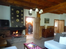 Un grand canapé d'angle, une table basse, une cheminée, vue sur la rocher du Dabo